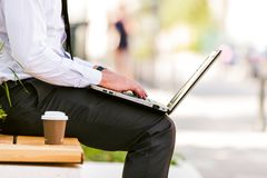 Young Business Man Drinking Coffee While Using Laptop. And Sitting At Bench Royalty Free Stock Photo