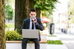 Young Business Man Drinking Coffee While Using Laptop. And Sitting At Bench Royalty Free Stock Image