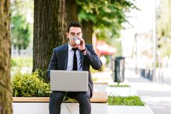 Young Business Man Drinking Coffee While Using Laptop. And Sitting At Bench Stock Images