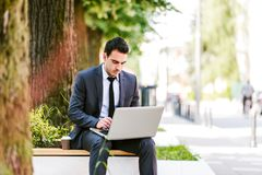 Young Business Man Drinking Coffee While Using Laptop. And Sitting At Bench Royalty Free Stock Photography