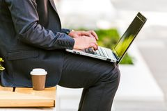 Young Business Man Drinking Coffee While Using Laptop. And Sitting At Bench Close up Stock Image