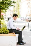 Young Business Man Drinking Coffee While Using Laptop. And Sitting At Bench Stock Photos