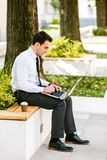 Young Business Man Drinking Coffee While Using Laptop. And Sitting At Bench Stock Photo