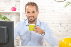 A young business man drinking a cup of coffee. On his office Royalty Free Stock Photography