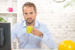 A young business man drinking a cup of coffee Stock Images
