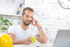 A young business man drinking a cup of coffee Stock Photo