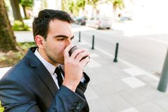 Young business man drinks coffee to go. While sitting outdoor Royalty Free Stock Photography