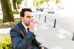 Young business man drinks coffee to go. While sitting outdoor Royalty Free Stock Image