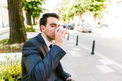 Young business man drinks coffee to go. While sitting outdoor Stock Photos