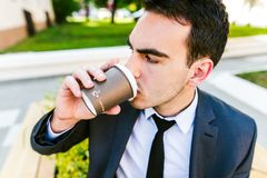Young business man drinks coffee to go. While sitting outdoor Stock Images