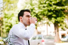 Young business man drinks coffee to go. While sitting outdoor Stock Image