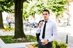 Young business man drinks coffee to go. While sitting outdoor Stock Photo