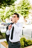 Young business Man drinks coffee to go. While standing outdoor Royalty Free Stock Photos