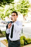 Young business Man drinks coffee to go. While standing outdoor Royalty Free Stock Images