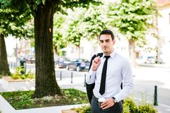 Young business Man drinks coffee to go. While standing outdoor Royalty Free Stock Image