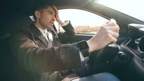 Young business man driving car very upset and stressed after hard failure and moving in traffic jam stock video footage