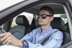 Young business man driving car wearing sunglasses Royalty Free Stock Photography