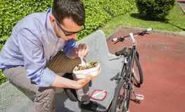 Young business man eating at lunch break outdoors Royalty Free Stock Photography