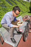 Young business man eating at lunch break outdoors Royalty Free Stock Images