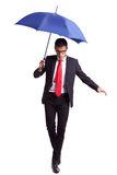 Young business man in an equilibrium act. Helped by an umbrella, walikng forward Royalty Free Stock Images