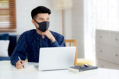 Young business man in face mask planning and working from home on laptop computer on desk.