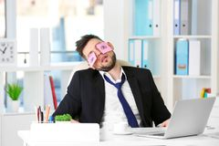 Young business man with fake eyes painted. On paper stickers sleeping at workplace in office Royalty Free Stock Photos