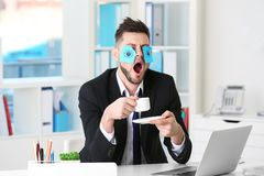 Young business man with fake eyes painted. On paper stickers yawning at workplace in office Stock Photography