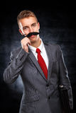 Young business man with fake mustaches Royalty Free Stock Photography