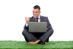 Young business man feeling ok. Young business man siting with lap top in his lap feeling happy and pleased looking at his nails Royalty Free Stock Images