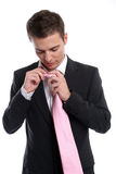 Young Business man, fixing his tie. Isolated in white background stock image