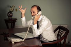 Young business man gesturing aggressive and talking on the phone Stock Images
