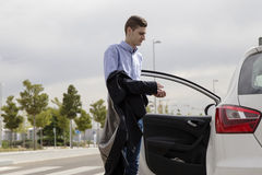Young business man getting inside white car. Young business man getting inside his white car Stock Image