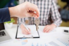 House key in hand. Young business man giving house with keys of customer at agency office Stock Photography