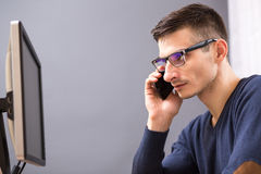 Young business man in glasses speaking on phone Stock Images