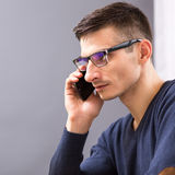 Young business man in glasses speaking on phone Royalty Free Stock Image