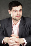 Young business man in gray suit. On gray background Royalty Free Stock Photography