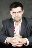 Young business man in gray suit. On gray background Stock Image