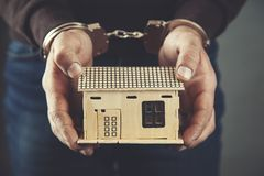 Man hand handcuffs and house model stock photography