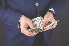 Young business man hand holding money on dark background royalty free stock photography