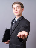 Young business man with hand out. A whiz kid boy dressed in a suit with computer and hand out for his allowance, donation or car keys Stock Image