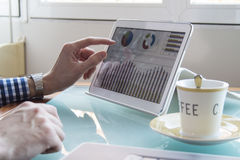 Young business man hands checking data on tablet screen and coffee on glass desk Royalty Free Stock Photo