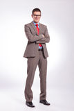Young business man with hands crossed. Full length picture of a young business man standing with his hands crossed and smiling for the camera. on a gray Stock Photography
