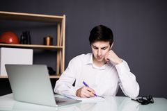 Young business man hands with pen writing notes on a paper. Male executive sitting at table at office. Close up shot of young business man hands with pen Stock Images