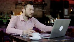 Young business man has turned upset working in a bar. Young business man has turned upset after reading something in the laptop working in a bar stock video