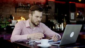 Young business man has turned upset working in a bar. Young business man has turned upset after reading something in the laptop working in a bar stock footage