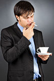 Young business man having a break drinking coffee and smoking a Royalty Free Stock Photo