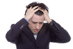 Young business man with a headache. Young worried and frustrated business man with a headache Stock Photography