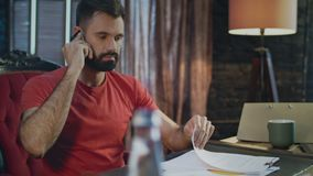 Young business man hearing bad news talking on phone in home office at evening. Man shock from business problem. Portrait of upset businessman talking on phone stock video footage