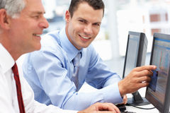 Young business man helping senior business man. On computers Royalty Free Stock Photo