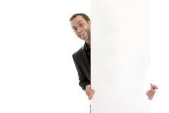 Young business man hiding behand an add space Royalty Free Stock Photos